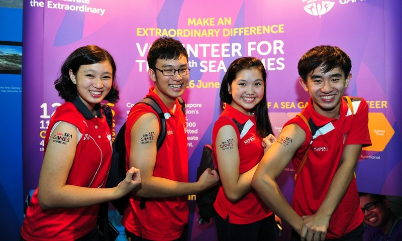Volunteers, helping out at the Singapore 2015 Launch Party, pose with their SEA Games temporary tattoos.
